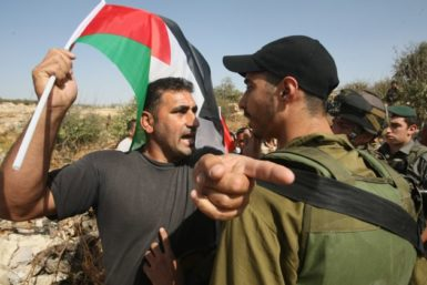 An Israeli soldier stopping Israelis, foreigners and Palestinian demonstrators as they try to reach Palestinian owned farm land, in the settlement of Karmi Tsour near the Palestinian village of Beit Omar in the West Bank, October 8, 2011
