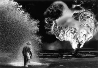 A firefighter under a protective chemical spray at Kuwait's Greater Burhan Oil Field, which retreating Iraqi troops had set on fire, 1991; photograph by Sebastião Salgado