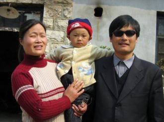 Chen Guangcheng with his wife and child outside their home in Dondshigu village, Shandong province, northeast China, March 28, 2005