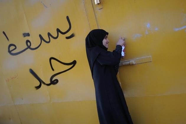 A Bahraini girl spraying slogans calling for the ouster of King Hamad bin Issa al-Khalifa, after the funeral for Abdelnabi Kadhim, Manama, November 24, 2011