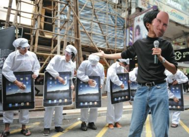 A man wearing a mask of Steve Jobs pretending to present new iPads outside an Apple store in Hong Kong, in a protest against conditions at Foxconn factories in China where Apple products are made, May 2011