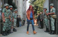 A woman passing soldiers outside a polling station in Cairo, December 5, 2011