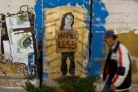 A man walking past graffiti, Athens,  December 6, 2011