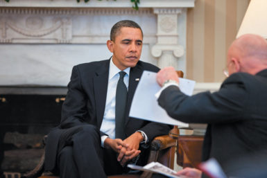 President Barack Obama studying a document held by Director of National Intelligence James Clapper during the presidential daily briefing in the Oval Office, February 3, 2011
