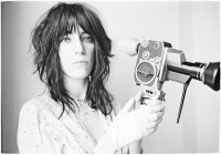 Patti Smith  holding the photographer Judy Linn's Super 8 Bolex camera at Linn's apartment in Brooklyn, early 1970s; from Linn's recent book of photographs, Patti Smith 1969–1976