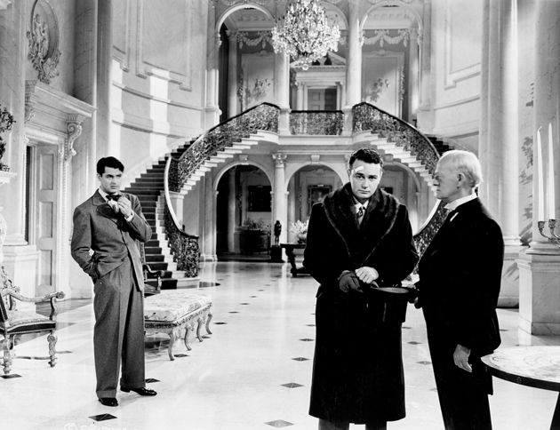 Cary Grant as Johnny Case, a self-made man, at his rich fiancée's house with her brother Ned (Lew Ayres) and the butler (Thomas Braidon), in George Cukor's Holiday, 1938