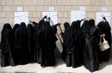 Yemeni women looking for their names on a registration list before voting in the presidential election that ended the thirty-three-year rule of Ali Abdullah Saleh, Sanaa, February 21, 2012