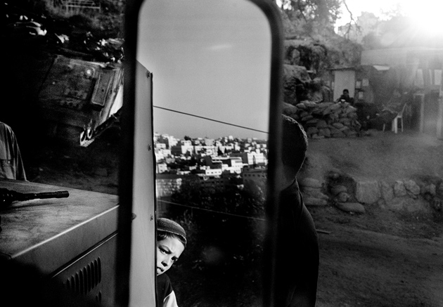 A young boy looking out at the city of Hebron from his family's trailer in the Jewish settlement of Tel Rumeida, 2002–2003