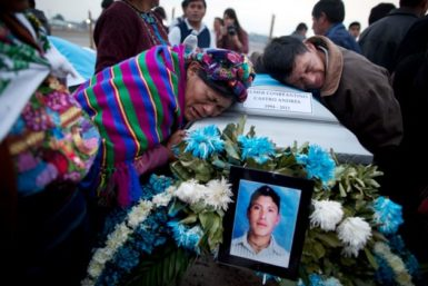 Natalia Andres Lopez and another relative mourn on the coffin containing the body of her cousin Elmer Constantino Castro Andrés at an Air Force base in Guatemala City, March 21, 2012. The remains of eleven Guatemalan citizens were repatriated from Mexico, part of 193 bodies found in the northern Mexico state of Tamaulipas in April 2011. Mexican authorities believe the dead were mostly migrants kidnapped from buses and killed by the Zetas drug cartel.