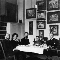 Henri Matisse (center) and Hans Purrmann (right) dining with Michael, Sarah, and Allan Stein at their apartment at 58 rue Madame, Paris, circa 1908. The paintings in the background, all by Matisse, are The Young Sailor I (far left); Pink Onions and Male Nude (left column); Fruit Trees in Blossom, Woman in a Kimono, Nude Reclining Woman, and Nude before a Screen (center column); Madame Matisse in the Olive Grove, a sketch for Le Bonheur de Vivre, and Madame Matisse (The Green Line) (right column).