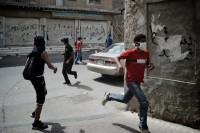 Bahraini youths run for cover as police fire teargas during Labor Day protests in the Manama suburb of Sanabis, May 1, 2012