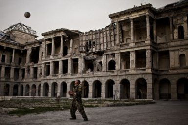 A young Afghan National Army soldier playing volleyball on the grounds of the battle-scarred Darulaman Palace outside Kabul, March 23, 2012. The former king's residence, the palace was destroyed in the 1990s during heavy fighting in Afghanistan's civil war.