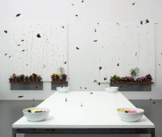 Damien Hirst: In and Out of Love (White Paintings and Live Butterflies), 1991. As Julian Bell writes, 'On a central table, the butterflies have been supplied with bowls of orange and pineapple chunks steeped in sugar, and the mixture's fermentation accounts for their languor.'
