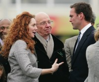 "Rebekah Brooks, then chief executive of Rupert Murdoch's company News International, with Murdoch and his son James at the Cheltenham Horse Racing Festival, March 18, 2010. Brooks resigned from News International in July 2011 after the Guardian reported that the News of the World had engaged in phone hacking in the early 2000s while she was its editor. In May 2012 she was charged with ""conspiracy to pervert the course of justice"" for concealing materials from police investigating phone hacking and bribery allegations."
