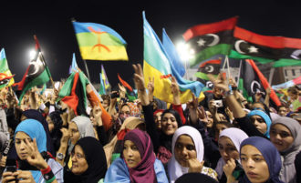 Libyan women waving the new Libyan flag (right) and the flag of the Amazigh people—often called Berbers—during an Amazigh festival in Tripoli, September 27, 2011. The indigenous Amazigh people are asking that a new Libyan constitution include official recognition of their language and culture, which had been prohibited by Muammar Qaddafi.