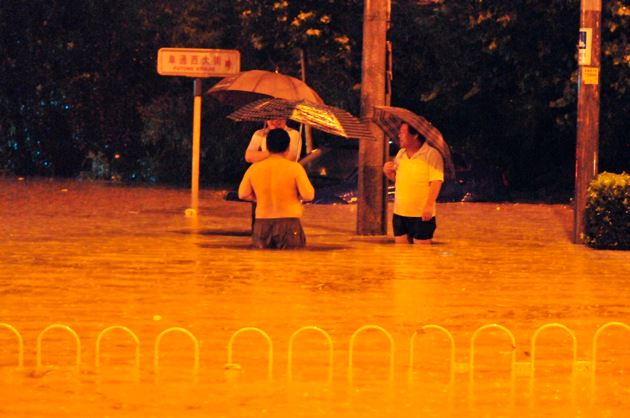 Pedestrians stand on a flooded street caused by heavy rain in Beijing, July 21, 2012