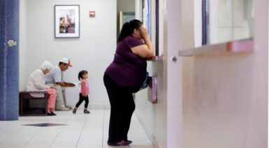 A woman stands at the registration window at Nuestra Clinica Del Valle in San Juan, Texas, July 12, 2012. About 85 percent of those served at the clinic are uninsured. The Texas Hospital Association estimates that care for uninsured patients cost hospitals in the state $4.5 billion in 2010.