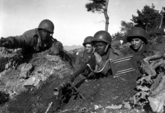 Somewhere north of the Chongchon River, while fighting with the 2nd Infantry Division, Sergeant First Class Major Cleveland, weapons squad leader, points out a communist-led North Korean position to his machine gun crew, Korea, November 1950