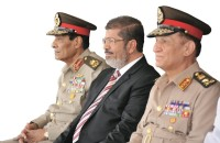 Newly elected Egyptian President Mohamed Mursi (center) with Field Marshal Mohamed Hussein Tantawi, head of Egypt's ruling Supreme Council of the Armed Forces (left), and Egyptian Armed Forces Chief of Staff Sami Anan (right), at a military ceremony in Alexandria, July 5, 2012