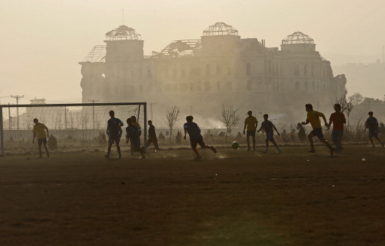 Afghan youth playing soccer in front of the ruins of the Dar ul-Aman Palace, Kabul, 2010