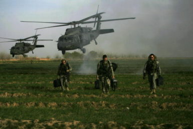 US army special forces walk in a field as Blackhawk helicopters transporting NATO officers land in Marjah's Balakino Bazar neighborhood on February 24, 2010.