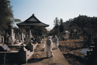 Mourners in protective clothing at a cemetery inside the nuclear exclusion zone, Fukushima, Japan, 2012