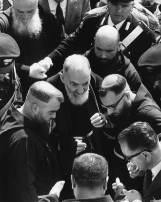 Padre Pio of Pietrelcina (center) with friars of the Capuchin order and several carabinieri, San Giovanni Rotondo, Italy, 1966
