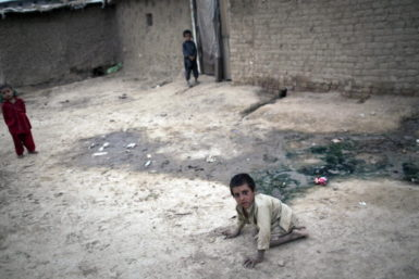 A child suffering from Polio outside his house near Islamabad, Pakistan, July 6, 2011