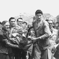 A wounded protester being carried away after an anti-Soviet demonstration, Berlin, June 17, 1953; the photographs on this page and page 48 are from Anne Applebaum's Iron Curtain: The Crushing of Eastern Europe, 1944–1956