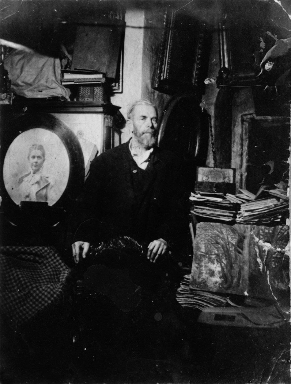 Count Pavel Sheremetev in his family's room in Naprudny Tower at the Novodevichy Monastery, Moscow, where they were sent to live after being expelled from their apartment outside Moscow in 1929. Surrounding him are the remains of the family archive and library, including a photograph of his late mother.