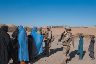 Female US Marines with Afghan women and children during a search-and-seizure operation, Helmand province, June 2010