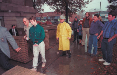 Jason Baldwin—one of three teenagers imprisoned for the murder of three eight-year-old boys in West Memphis, Arkansas—being led to a pretrial hearing past the fathers of the ­murdered boys, November 16, 1993. From right to left are Steven Branch, father of Steven Branch; Todd Moore, father of Michael Moore; and John Mark Byers, stepfather of Christopher Byers.