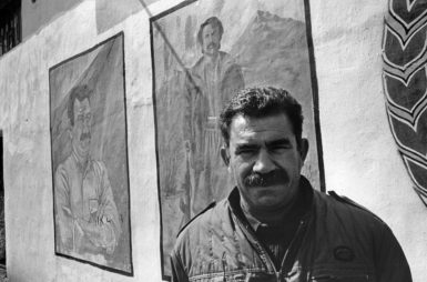 Abdullah Öcalan, leader of the Kurdistan Workers' Party (PKK), at a PKK training camp, Bekaa Valley, Lebanon, 1991. He is now imprisoned on the Turkish island of Imrali. The paintings in the background are of Öcalan, left, and a PKK soldier killed in battle.