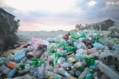 A boy sleeping in a pile of plastic bottles at the Truitier landfill, Cité Soleil, Port-au-Prince, Haiti, April 2011