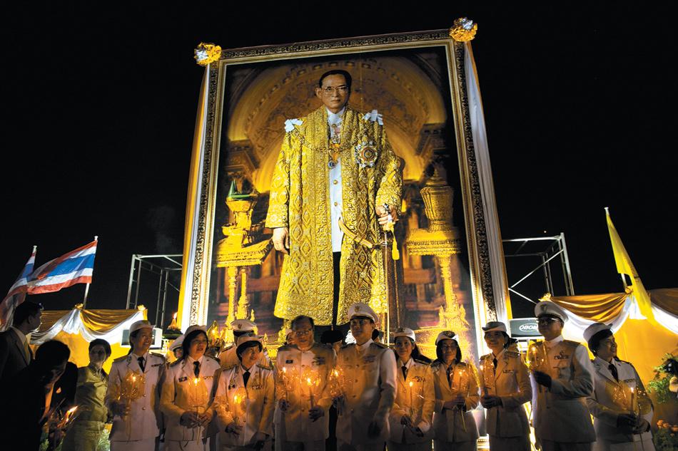 Thai royal nurses holding candles at a celebration of King Bhumibol Adulyadej's eighty-fifth birthday, Bangkok, December 2012