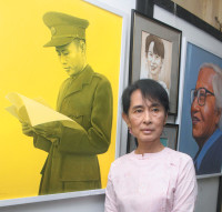 Aung San Suu Kyi standing in front of a painting of her father, General Aung San, Rangoon, October 2011