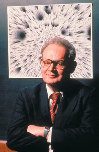 Benoit Mandelbrot, 1982. Behind him is an attempted computer simulation of a crater field. Crater fields, such as those occurring on the moon, are formed by the cumulative impact of meteorites. They have a fractal structure, one that can be mimicked by computer methods. But the program that generated this not very plausible lunar landscape contained an error, leading Mandelbrot to dub the image 'the computer bug as artist.'