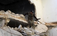 A Syrian rebel fighter descending from a damaged building, Aleppo, Syria, June 12, 2013