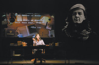 Moe Angelos as the young Susan Sontag in the play Sontag: Reborn, with an image of Angelos as an older Sontag at right, projected onto the scrim in front of the stage