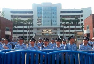 Police stand guard during a protest, Jiangmen city, Heshan, Guangdong, July 12, 2013