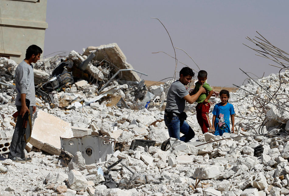 A man helping a boy through the rubble of a damaged house near Hama, Syria, September 13, 2013