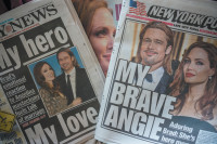 Newspapers showing front-page coverage of Angelina Jolie's decision to have a preemptive double mastectomy to reduce her risk of breast cancer after genetic testing showed that she carried the abnormal BRCA1 gene, May 15, 2013