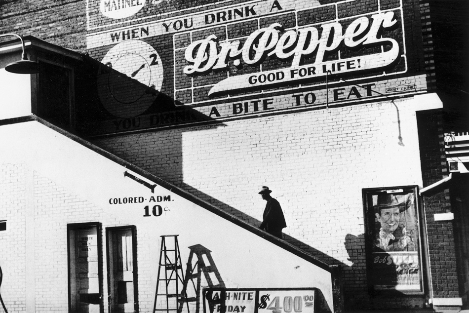 An African-American entering a movie theater through the segregated back entrance, Mississippi, October 1939; photograph by Marion Post Wolcott for the Farm Security Administration