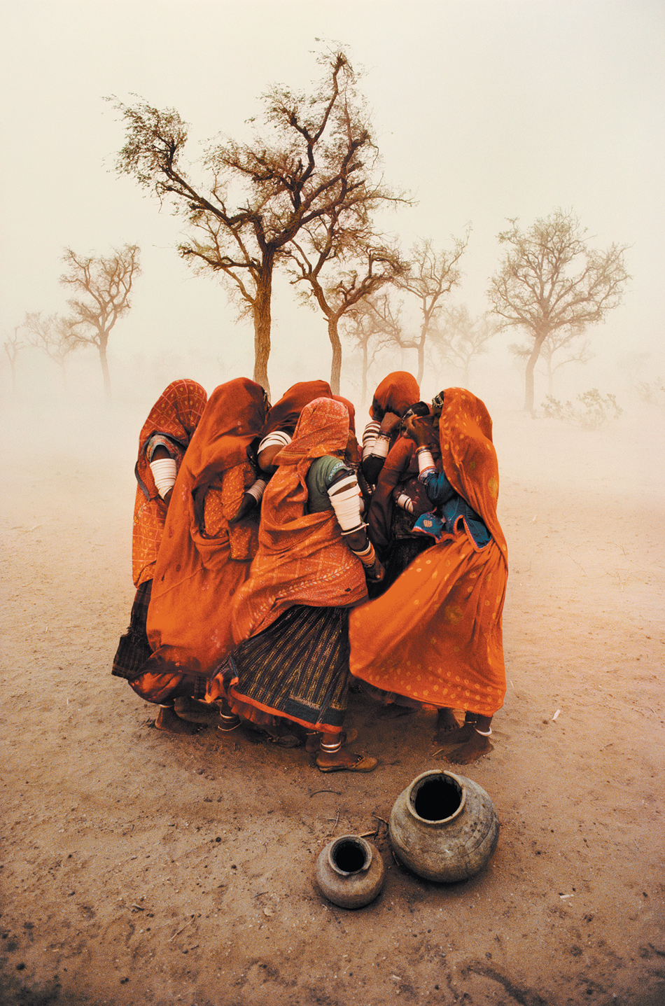 Women shielding themselves from a dust storm, Rajasthan, India, 1983; photograph by Steve McCurry from his book Untold: The Stories Behind the Photographs, which includes fourteen of his photo stories from India, Afghanistan, Cambodia, and other countries, along with essays about his work and ephemera from his personal archive. It has just been published by Phaidon.