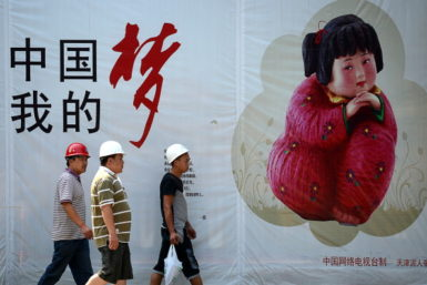 """Workers walking past a """"China Dream"""" poster, Beijing, September 2, 2013"""