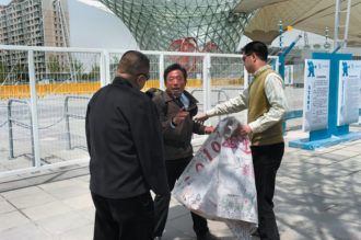 An umbrella salesman being arrested by two plainclothes officers a moment after unfurling an apparently apolitical, sports-related banner in front of the Shanghai World Expo (hoping it would be captured by the foreign photographer who was nearby), April 2010