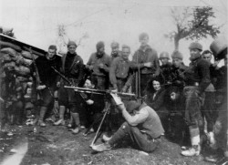 George Orwell (standing behind the machine-gunner) and his wife Eileen (crouching at Orwell's feet) with the British Independent Labour Party contingent at the Huesca Front during the Spanish Civil War, March 1937