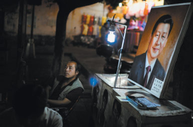 A street artist with his portrait of Chinese President Xi Jinping, Dali, China, July 2013