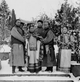 The Dowager Empress Cixi with four eunuchs and Der Ling, a lady-in-waiting, circa 1903–1905