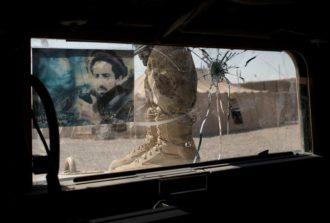 An Afghan officer after a patrol in Helmand Province, Afghanistan; the image on his vehicle's windshield depicts anti-Taliban warrior Ahmed Shah Masood, October 19, 2012